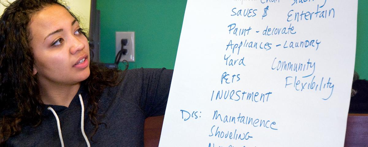 Woman examining easel sheet with notes on financial literacy