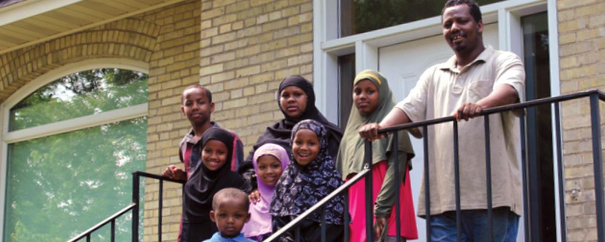 A family of seven on the steps outside a newly purchased brick home