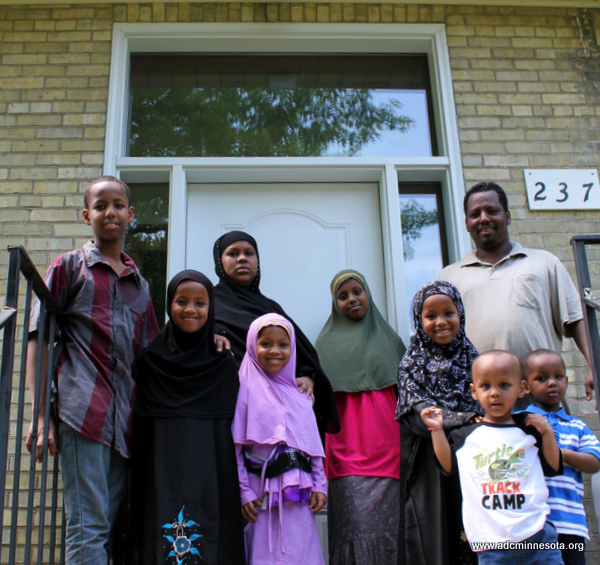 a somali family of nine outside their new home