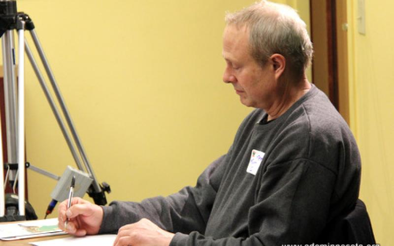 A participant takes notes during the presentation