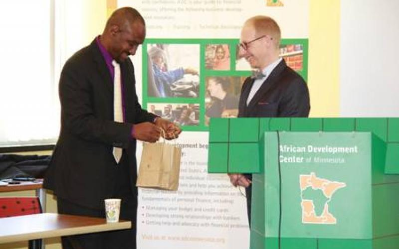 Nasibu Sera presents Jeremy Hanson Willis a thank you gift in a brown bag