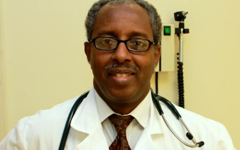 Dr. Mohamud Afgarshe in lab coat with stethoscope around his neck