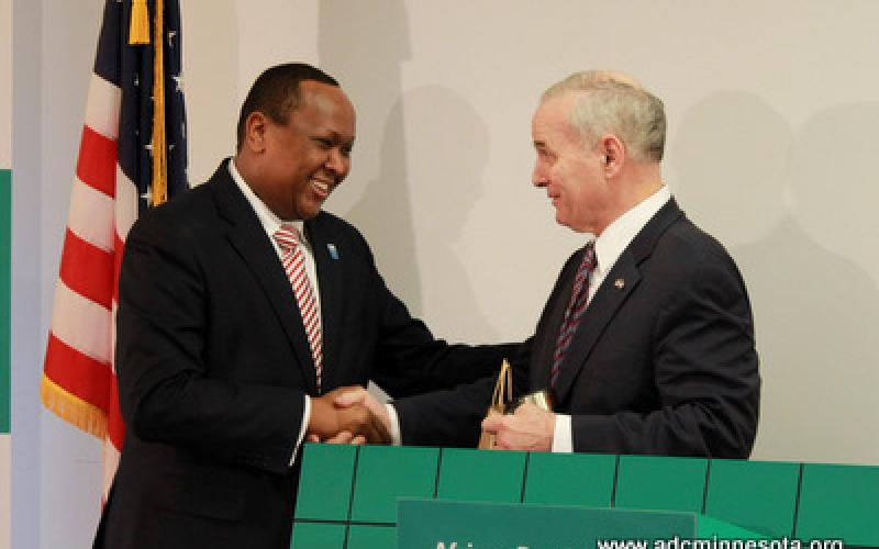 Hussein Samatar shakes Governor Mark Dayton's hand at the podium