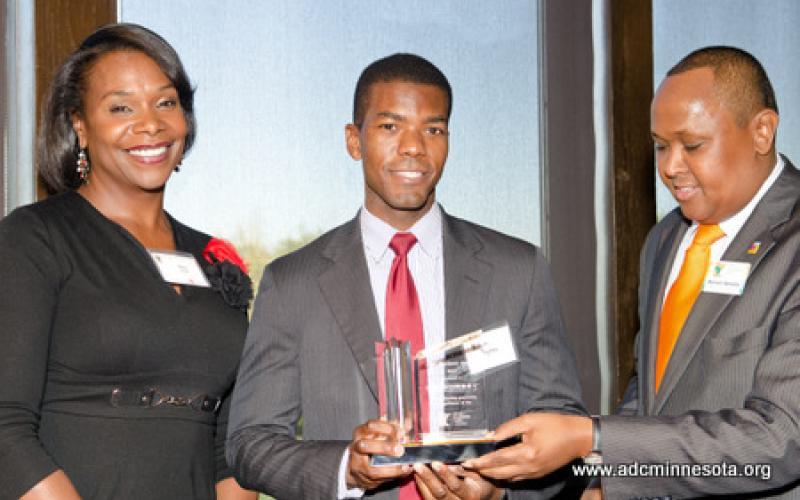 An awards recipient stands with Hussein Samatar