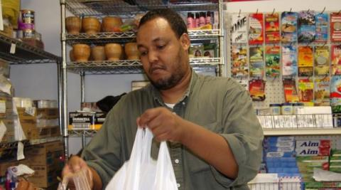 Photo of Abdiqafar Adan bagging a customer purchase in his grocery