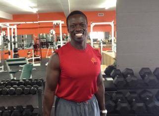 Stephen Menya standing with barbells among free weights.